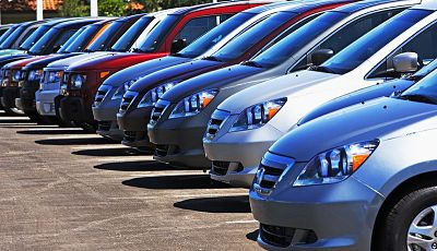 A line of brand new rental cars in a parking lot.